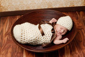 Newborn baby girl sleeping in a crocheted cream colored cocoon She is wearing a matching beanie hat and lying in a brown bowl — Stock Photo