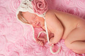 Newborn baby girl wearing a cream colored crocheted bonnet and sleeping on pink rose field fabric. — Stock Photo