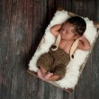 Stock Photo: Newborn Baby Boy Sleeping in a Rustic Crate