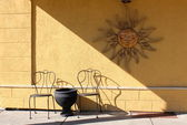 Yellow painted stucco wall with old rustic metal sun decoration hanging over black metal chairs and table at outdoor eatery — Stock Photo