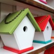 Handcrafted rustic birdhouses with bright colorful roofs and link chains for hanging them up around the yard to attract our feathered friends to nest in. — Stock Photo #25742851