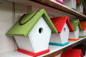 Handcrafted rustic birdhouses with bright colorful roofs and link chains for hanging them up around the yard to attract our feathered friends to nest in. — 图库照片