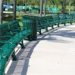 Neat and orderly semi circle arrangement of green metal benches in park — Stock Photo #26440983