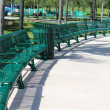 Neat and orderly semi circle arrangement of green metal benches in the park — Stock Photo #26440983