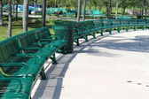 Neat and orderly semi circle arrangement of green metal benches in the park — Stock Photo