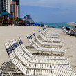 Long line of lounge chairs inviting vacationers to sit and enjoy the beach for the day — Stock Photo
