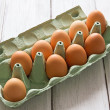 Eggs in egg-box on white wood background — Stock Photo