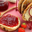 Strawberry jam on toasted teacake - Stock Photo