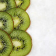 Italian kiwi fruit slices on white marble background — ストック写真