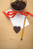 Chocolate cookie-heart on a piece of paper with pencil — Stock Photo