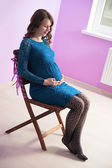 The pregnant woman in sapphirine dress is sitting on the chair — Stockfoto