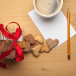 The cup of coffee on the table with a piece of paper, pencil and cookie-hearts — Stock Photo