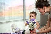 Een klein meisje is verheugd door bloemen — Stockfoto