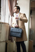 Young and handsome businessman looking out of the window — Stock Photo