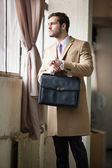 Elegant young businessman looking out the window. — Stock Photo