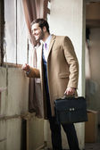Empresário jovem e bonito, olhando pela janela — Fotografia Stock