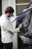 Handsome man shopping for clothes at a store. — Stock Photo