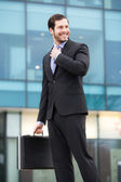 Smiling businessman in front of an office building — Stock Photo