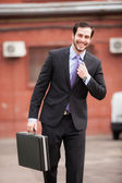 Smiling businessman walking on the street — Stock Photo