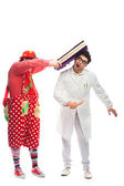 Crazy doctor and clowns playing on white background — Stock Photo