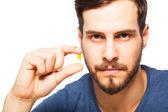 Handsome man showing pills  — Stockfoto