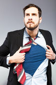 Young businessman acting like a super hero — Stockfoto
