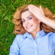 Beautiful young woman relaxing in grass — Stock Photo #50449281
