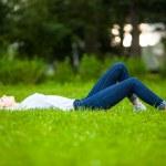 Beautiful young woman relaxing in grass — Stock Photo #50449463