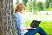 Beautiful woman sitting in park with laptop — Stock Photo