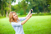 Nice woman taking pictures with smartphone — Stock Photo