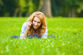 Blonde woman speaking at cellphone in green grass — Foto de Stock