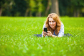 Blonde woman speaking at cellphone in green grass — Photo