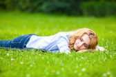 Smiling blonde woman in green grass showing love — Stock Photo