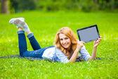 Блондинка женщина, лежа на зеленой траве с планшетом в руках — Стоковое фото