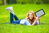 Blonde frau in grünem gras mit einem grafiktablett in händen — Stockfoto