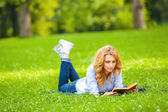 Woman lying in grass and reading a book — Photo
