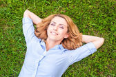 Beautiful young woman relaxing in grass — Stock Photo