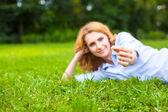 Beautiful young woman relaxing in grass — Stock Photo