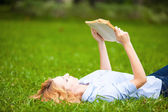 Woman lying in grass and reading a book — Foto de Stock