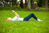 Pretty young blonde woman lying in grass using a tablet — Photo