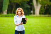 Young lady with tablet in park — Stok fotoğraf