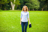 Young lady with tablet in park — Stock Photo