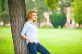 Beautiful young woman standing next to a tree — Stock Photo