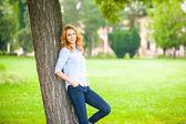 Hermosa joven de pie junto a un árbol — Foto de Stock