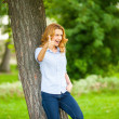 Beautiful young woman standing next to a tree — Stock Photo #50450011