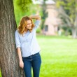 Beautiful young woman standing next to a tree — Stock Photo #50450059
