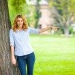 Beautiful young woman standing next to a tree — Stock Photo #50450117