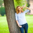 Beautiful young woman standing next to a tree — Stock Photo #50450141