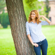 Beautiful young woman standing next to a tree — Stock Photo #50450153