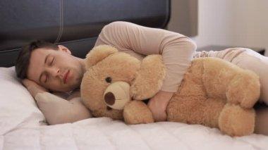 Guy is sleeping with teddy bear — Stock Video